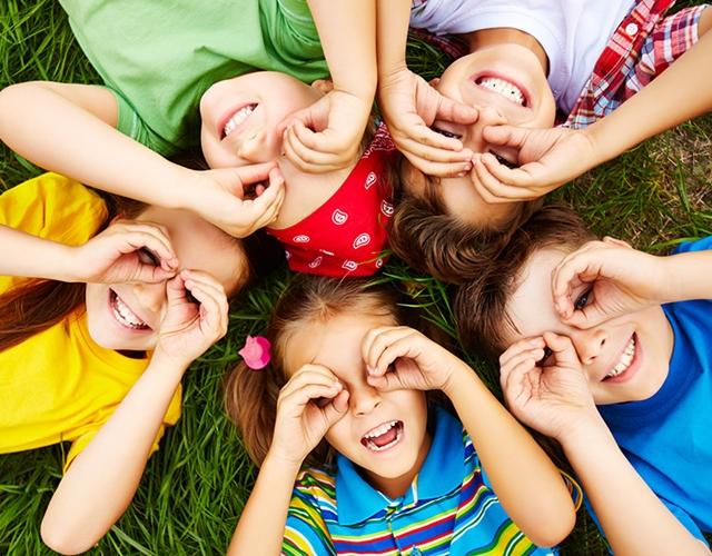 cinq jeunes enfants allongés sur l'herbe