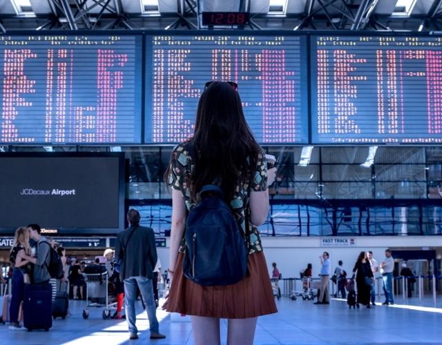 jeune fille debout devant affichage aéroport