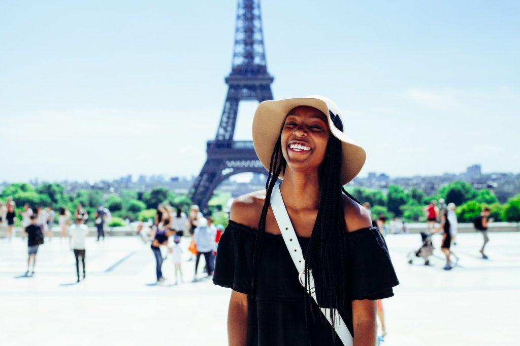 jeune fille très souriante devant Tour Eiffel